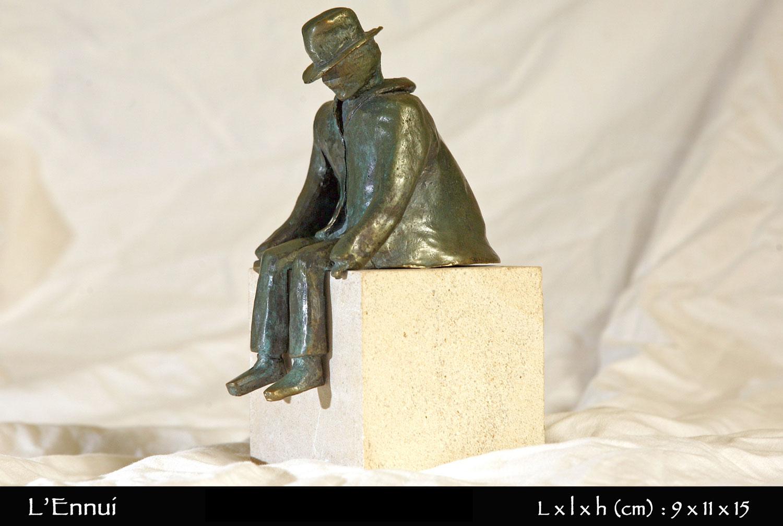 Personnage en bronze assis sur une pierre