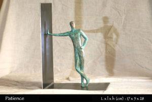 Personnage en bronze attendant patiemment