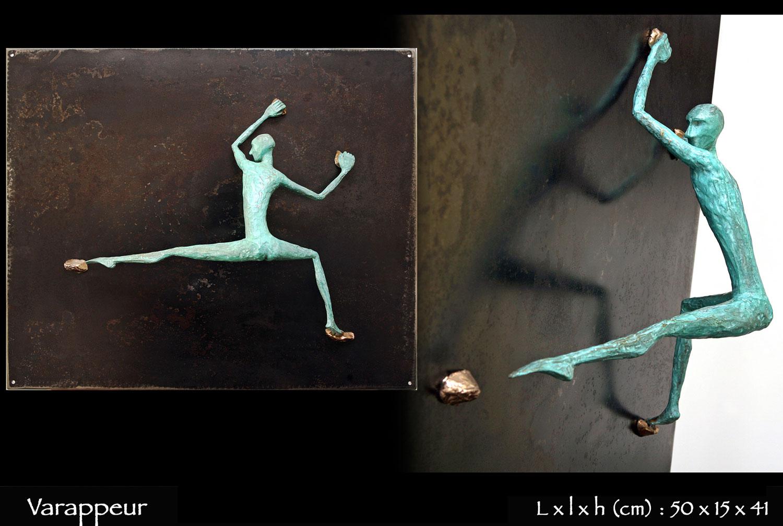 Personnage en bronze faisant de la varappe sur une paroi en métal