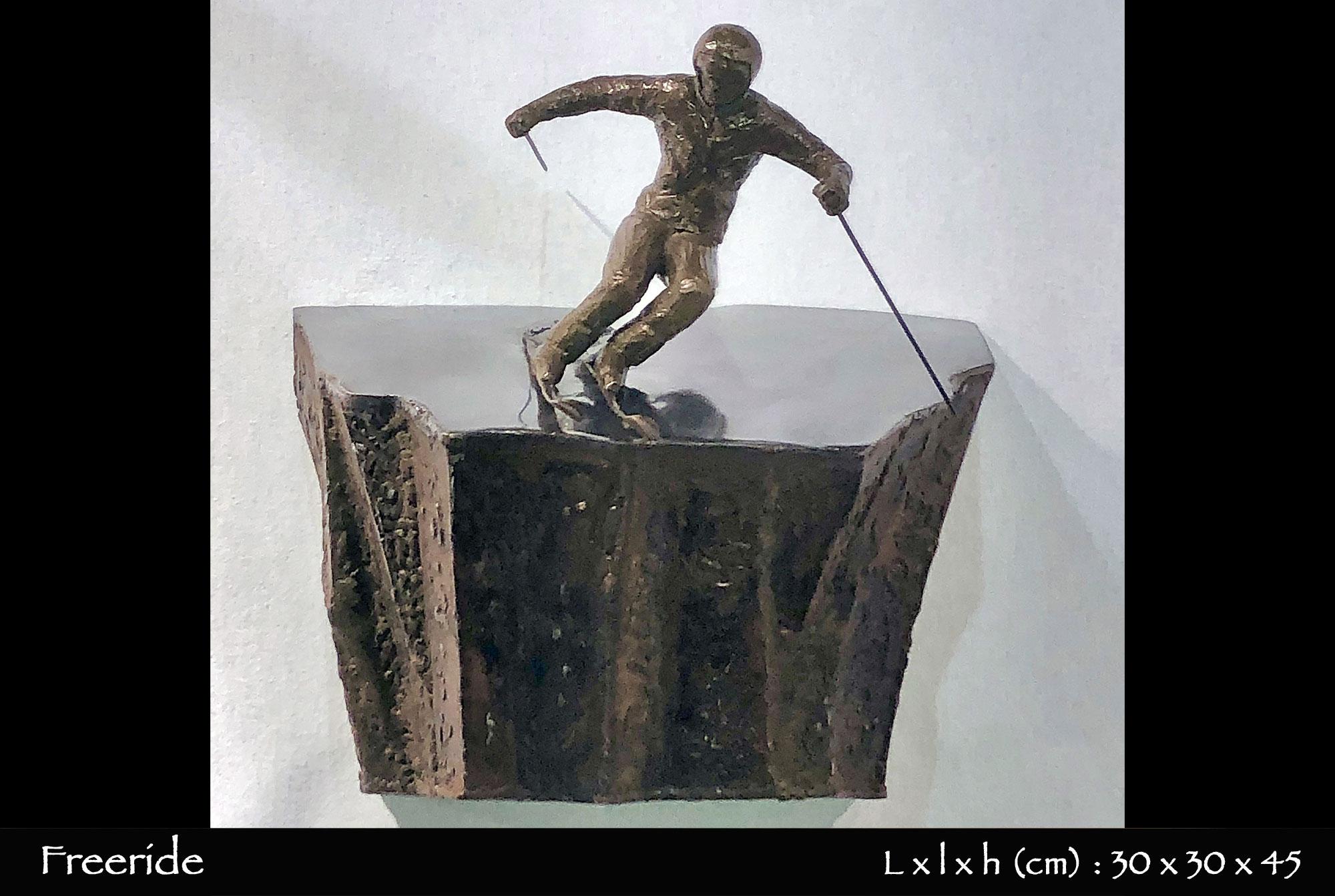 Skieur en bronze sautant d'une barre rocheuse