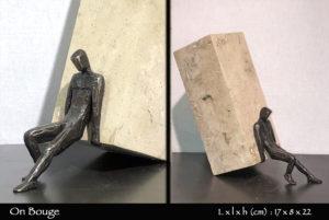 personnage en bronze poussant une pierre