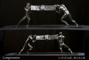 Personnages en bronze de deux hommes comprimant une barre d'acier