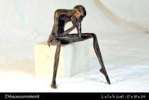 Personnage en bronze désoeuvré, assis sur sa pierre