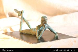 Personnage en bronze allongé par terre