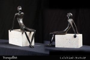 Personnage en bronze tranquillement assis sur une pierre