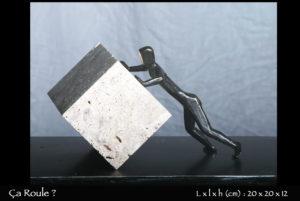 Personnage en bronze faisant rouler une pierre carrée