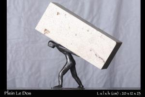 personnage en bronze portant une pierre sur son dos