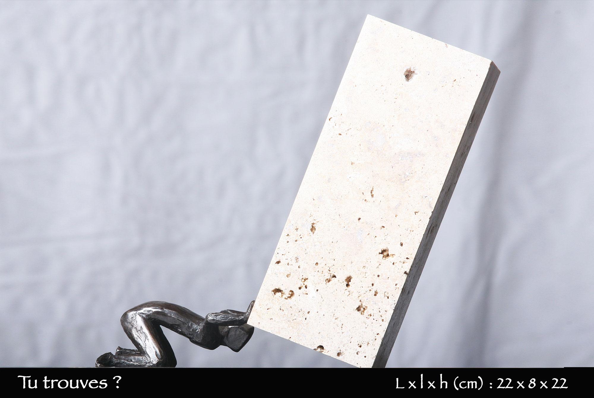 personnage en bronze cherchant sous une pierre