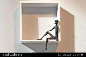 personnage en bronze assis sur le rebord d'une étagère